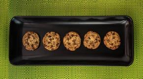 Pięć czekoladowego układu scalonego ciastek w czarnym pucharze na zielonym tablecloth zdjęcie stock