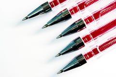 Pięć czerwonych piór z czerwonym prąciem na białym tle, błyszczące cząsteczki Zdjęcie Royalty Free
