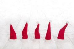 Pięć czerwonych Santa kapeluszy na śnieżnego bielu drewnianym tle dla Christm Fotografia Royalty Free