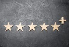 Pięć drewnianych gwiazd i a plus na betonowym szarym tle, Pojęcie wysoki cenienie ilość i usługa Zdjęcie Stock