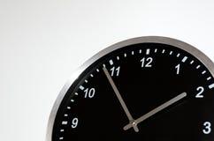 Pięć, dwa ustawia na czarnym ściennym zegarze Obrazy Royalty Free