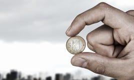 Pięć euro moneta między palcami Mieszani środki fotografia stock
