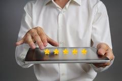 Pięć gwiazdowa ocena lub ranking porównywać z normą pojęcie, Mężczyzna z pastylka pecetem ocenia usługa, hotel, restauracja Obrazy Stock