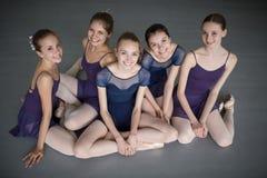 Pięć młodych balerin siedzi na podłoga Zdjęcia Stock