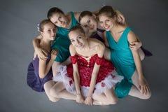 Pięć młodych balerin siedzi na podłoga i patrzeje ca Obrazy Royalty Free