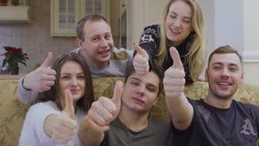 Pięć młodych caucasian przyjaciół spojrzeń przy kamerą i przedstawienie aprobatami zbiory