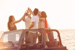 Pięć młodzi ludzie ma zabawę w odwracalnym samochodzie przy plażą przy zmierzchem obraz stock