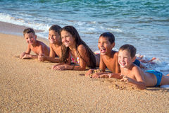 Pięć ono uśmiecha się dzieciaków łgarskich puszków na plaży Zdjęcia Royalty Free