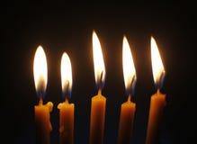 Pięć płonących wosków świeczek na czarnym tła zakończeniu up Obrazy Stock