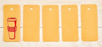 Pięć przetwarzających papierów etykietek z ślicznym różowym rysunkiem filiżanka i puste miejsce na białym drewnianym tle Fotografia Royalty Free