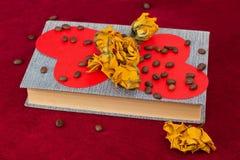 Pięć róż i dwa serca kłama na książce z kawowymi fasolami fotografia stock