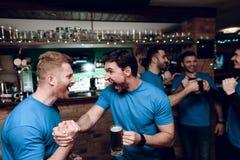 Pięć sportów fan pije niedźwiadkowego doping przy sporta barem Trząść ręki w świętowaniu zdjęcie stock