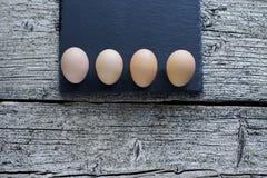 Pięć surowych kurczaków jajek kłamają na czarnej desce na drewnianym tle zdjęcie stock