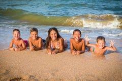 Pięć szczęśliwych dzieciaków łgarskich puszków na plaży wpólnie Fotografia Royalty Free