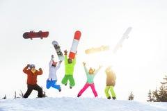 Pięć szczęśliwych przyjaciół snowboarders skaczą i mieć zabawę Obrazy Stock