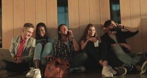 Pięć szczęśliwych wielokulturowych modnisiów przyjaciół gawędzą, surfują internet i opowiadają przez telefonu komórkowego, podcza zdjęcie wideo