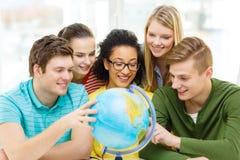 Pięć uśmiechnięta studencka patrzeje kula ziemska przy szkołą obraz stock