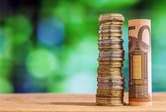 Pięćdziesiąt euro staczał się rachunku banknot z euro monetami na zielonym blurre, Obraz Royalty Free