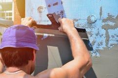 Pięćdziesiąt lat ręczny pracownik z ściennym gipsowaniem wytłacza wzory odnawić dom obraz royalty free