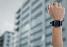 Pięść w powietrzu z zegarkiem przeciw rozmytemu budynkowi Zdjęcie Stock