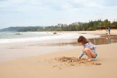 Pięcioletnia dziewczyna bawić się na piaskowatej plaży morze obrazy stock