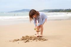 Pięcioletnia dziewczyna bawić się na piaskowatej plaży morze obraz royalty free