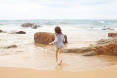 Pięcioletnia dziewczyna bawić się na piaskowatej plaży morze zdjęcia stock