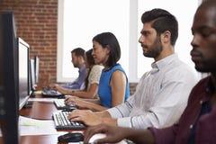 Pięcioliniowy obsiadanie Przy biurkami Używać komputer W Ruchliwie biurze obraz stock