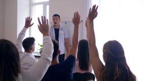 Pięcioliniowy szkolenie, pomyślni ludzie podwyżek ręk do części myśli z trenerem i widownia na konwersatorium, zdjęcie wideo