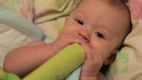 Pięciomiesięczny dziecko stawia w jego usta zabawkę zbiory