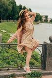 piękną dziewczynę złotowłosy czerwony obrazek przeciw tłu rzeka, woda, jezioro w parku, lato wiatr kłuje up oblamowanie zdjęcie royalty free