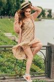 piękną dziewczynę złotowłosy czerwony obrazek przeciw tłu rzeka, woda, jezioro w parku, lato wiatr kłuje up oblamowanie zdjęcie stock