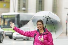 Piękna łacińska kobieta hitchhiking w ulicie z parasolem obraz stock