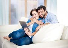 Piękna łacińska para w miłości kłama wpólnie na żywej izbowej kanapy leżance cieszy się używać cyfrową pastylkę zdjęcie stock