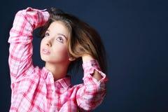 Piękna ładna dziewczyna trzyma włosiany i patrzeje up Obraz Stock