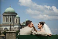 Piękna ślub para siedzi na ławce przed kościół. Obraz Stock
