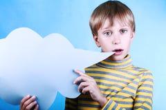 Piękna śmieszna blond chłopiec trzyma pustej błękitnej wiadomości obłocznego saying coś Fotografia Stock