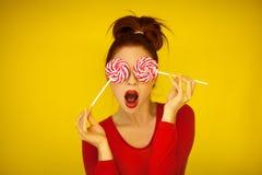 Piękna śmieszna kobieta w czerwonym i żółtym mieniu dwa wiruje lizaki zdjęcie royalty free