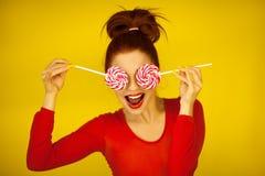 Piękna śmieszna kobieta w czerwonym i żółtym mieniu dwa wiruje lizaki obraz stock