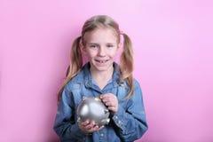 Piękna śmieszna młoda dziewczyna z srebnym prosiątko bankiem na różowym tle koncepcja pieniędzy, żeby ratować obraz royalty free