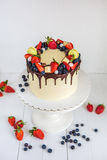 Piękna śmietanka barwił tortowego dekorującego z truskawkami, czarne jagody, czekolada, macaroon, stoi na białym drewnianym stole zdjęcie royalty free