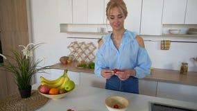 Piękna żeńska gospodyni domowa przygotowywa zdrowego śniadanie z uśmiechem i stojaki przy stołem w nowożytnej jaskrawej kuchni w  zbiory