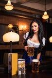 Piękna żeńska kelnerka jest ubranym tradycyjnego dirndl i trzyma ogromnych piwa w pubie Obrazy Royalty Free