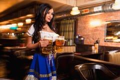 Piękna żeńska kelnerka jest ubranym tradycyjnego dirndl i trzyma ogromnych piwa w pubie Obraz Royalty Free