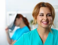 Piękna żeńska medycyny lekarka śmia się na jej koledze obraz royalty free