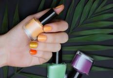 Piękna żeńska ręka z żółtym gwoździa projektem z błyskotliwością zdjęcia stock