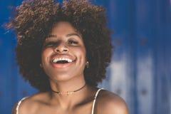 Piękna afro amerykańska kobieta śmia się na błękitnym tle Fotografia Royalty Free