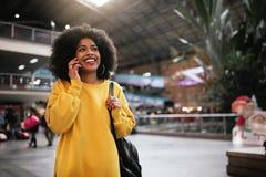 Piękna afro kobieta używa wiszącą ozdobę w dworcu Obrazy Royalty Free