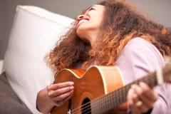 Piękna afroamerican dziewczyna bawić się gitarę Obrazy Royalty Free