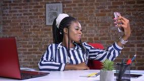 Piękna afrykańska dziewczyna bierze selfie i ono uśmiecha się podczas gdy siedzący przy jej miejscem pracy w czerwonym biurze zbiory